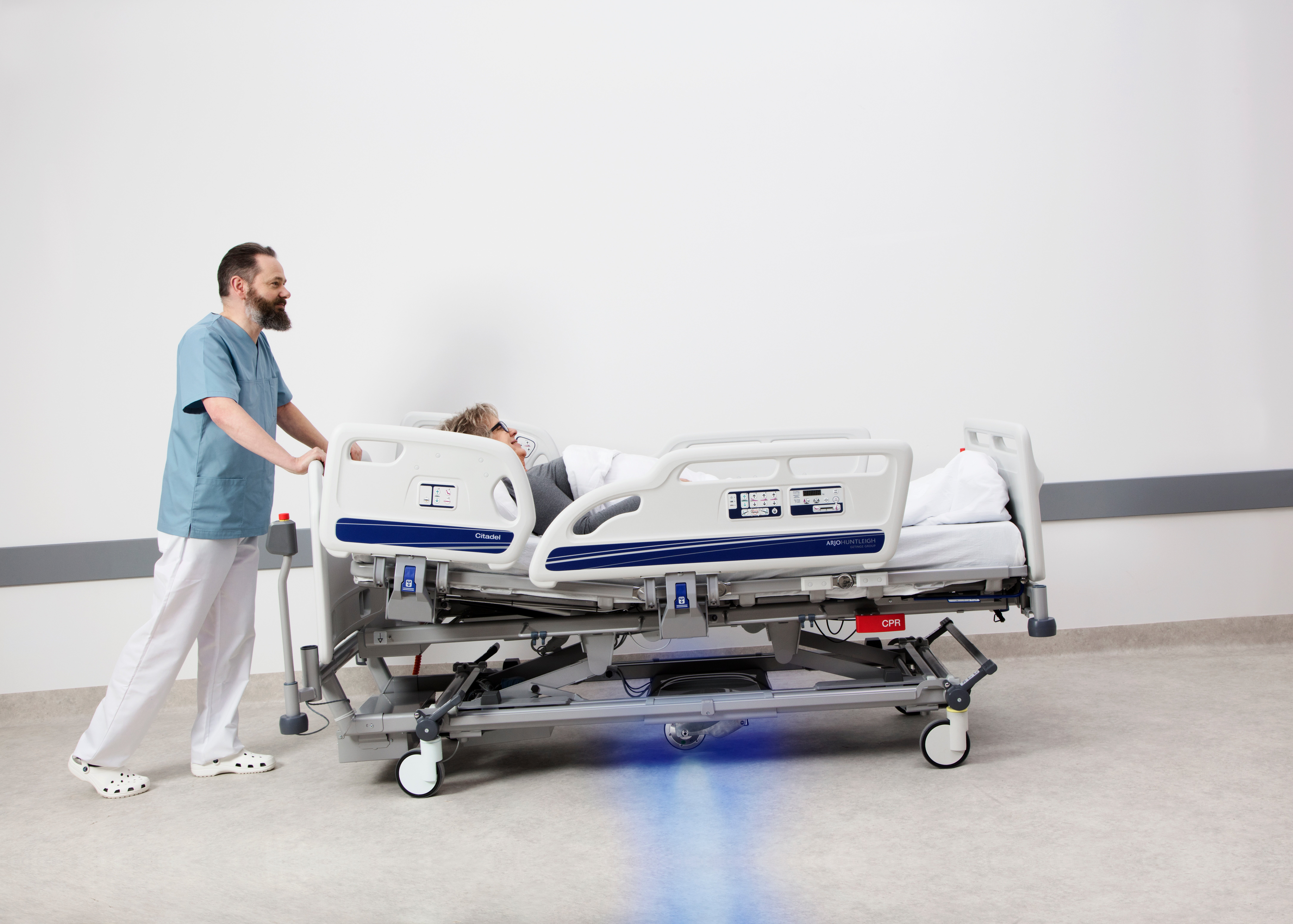 Which technologies are used to aid caregivers in transporting patients on hospital beds?